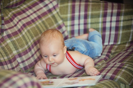 Knowledge, education, literature. Baby boy read book on sofa. Infant wear jeans and suspenders at home. Child development concept. Childhood, infancy, innocence. 版權商用圖片