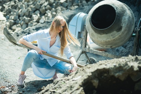 Fashion girl work at construction, vogue. Woman worker in shirt and jeans on building site, fashion. Woman with long blond hair, hairstyle hold shovel. Beauty model with makeup at cement mixer. Reklamní fotografie