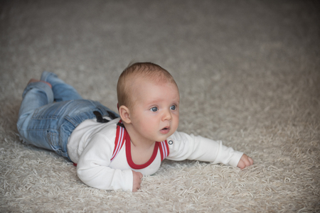 Baby with blue eyes on adorable face. Child development concept. Infant crawl on floor carpet. Childhood, infancy, newborn. Innocence, beauty, purity. Stok Fotoğraf