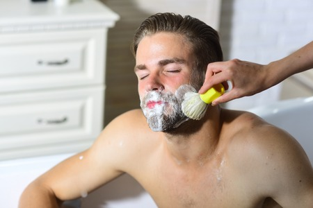 Bearded man getting shaving foam applied on beard with brush. Skincare, treatment, therapy. Grooming, hygiene, health. Barber, barbershop, salon. Stock fotó