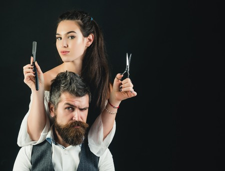 Young handsome man with long beard and moustache on serious face with young woman cutting with scissors