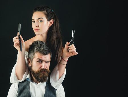 Junger gutaussehender Mann mit langem Bart und Schnurrbart auf ernstem Gesicht mit der jungen Frau , die mit Scheren schneidet Standard-Bild