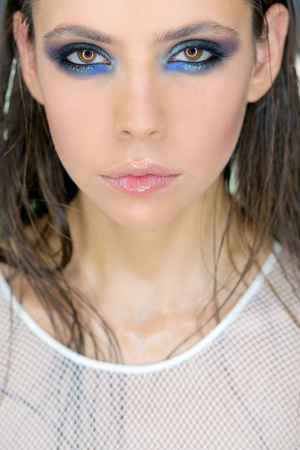 Girl with bright eye makeup face skin, skincare. Woman with oily long hair in beauty salon. Fashion model with glamour look, makeup. Hair care and skincare, therapy, treatment concept. 写真素材