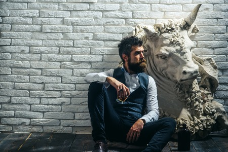 Bearded man collector drink whiskey at plaster statue. bearded man sculptor at bull statue on brick wall background, white, copy space Stock fotó