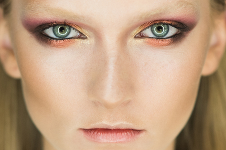 Blue eye of woman with beautiful golden shades and black eyeliner makeup. Classic make up. Perfect brows nose and lips. look