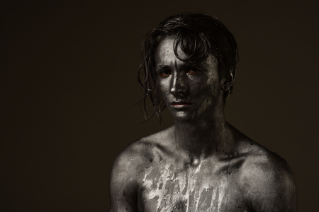 Handsome man of athletic build, completely covered in silver paint on black background, copy space, black and white