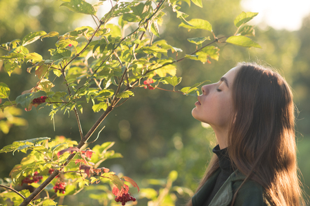 spring time! young girl at viburnum or rowan tree sunny outdoor. woman stand near tree in spring. spa therapy and treatment, nature. beauty and youth fashion. 写真素材 - 98726251