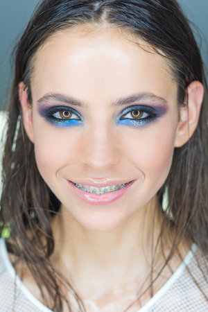 Woman with braces on teeth. Happy girl smile with dental braces. Woman smiling with bright eye makeup and long hair, beauty. Dental health concept. Beauty model with glamour look, make up. 版權商用圖片