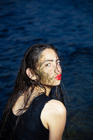 Spa Outdoor, Beautiful young woman with natural dead sea face mask. woman in the mud. dirty woman in Dead sea. Young woman enjoy natural mineral mud sourced from Dead sea. Banque d'images - 98674625
