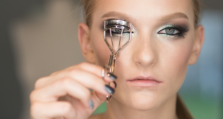 Look, woman use eyelash curler for eye makeup. Look of beauty woman with curly long eyelashes.