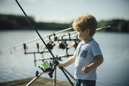 Childhood, education, training. Little boy learn to catch fish in lake or river. Summer vacation, hobby, lifestyle. Child with fishing rod on wooden pier. Fishing, angling, activity, adventure, sport.