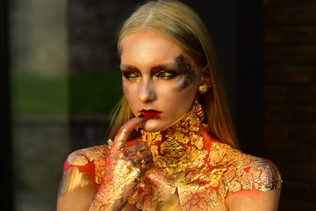 Woman with art make up, creative bodyart. Woman with blond hair, golden foil on skin, cosmetics.