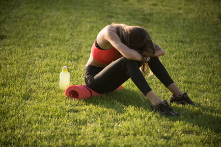 Tired woman in sportswear relax after workout, training. Sportswoman sit on green grass with gym equipment on summer. Backache, back pain, fatigue. Sport, training, workout. Health, bodycare, wellness Stockfoto
