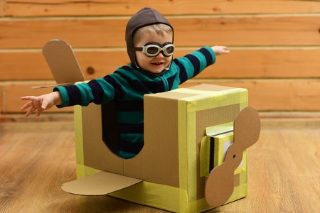 Dream, career, adventure, education. Pilot travel, airdrome, imagination. Air mail delivery, aircraft construction. Little boy child play in cardboard plane, childhood. Kid, pilot school, innovation.