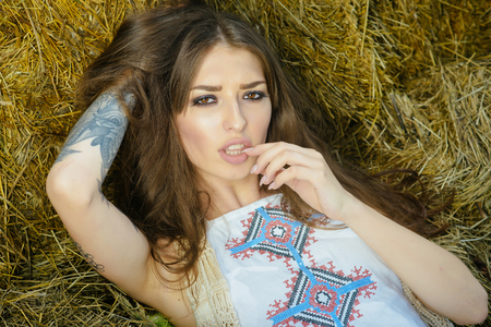 Pretty young country woman on bales of hay in barn.