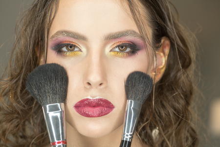 Beauty woman with makeup brushes, visage. Beauty model apply powder on face.
