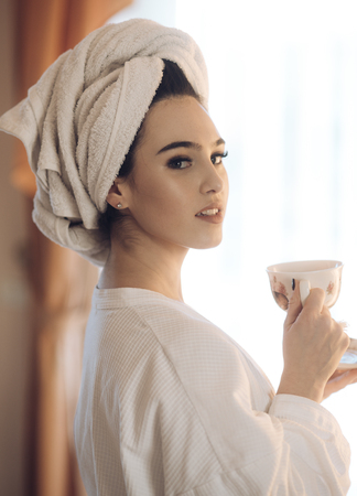 Girl with towel on head enjoys morning coffee after shower. Sexy lady with mysterious face drinks coffee. Morning coffee concept. Woman in bathrobe with window on background.
