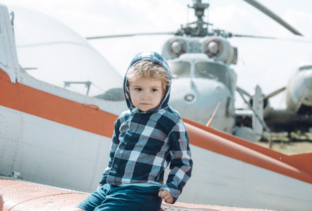 Cute boy sits on wing of old plane in aviation museum. Textured grunge old helicopter and sky with clouds on background. Kid on excursion to museum of aviation in open air. Air forces history concept. Imagens - 99543381