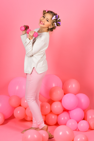 weight lifting, pink background. weight lifting of little girl in pink studio, gym Reklamní fotografie