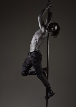 Guy hanging on metallis pole. Athlete, sportsman performing pole dancing moves, work out, show trick. Performance concept. Man with nude torso covered with shimmering silver paint, dark background.