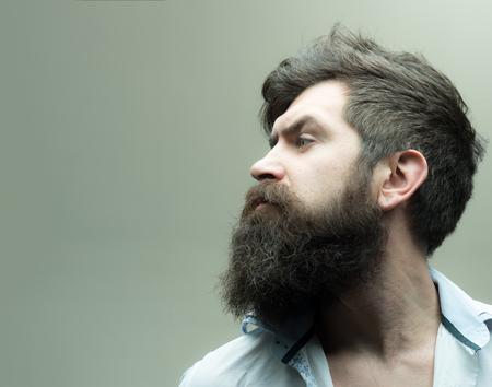 Concept de salon de coiffure ou de coiffeur. Macho sur le visage strict, porte une chemise déboutonnée. Homme avec barbe, moustache et cheveux élégants, fond clair. Guy avec une coiffure moderne a visité le coiffeur, vue latérale. Banque d'images