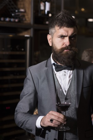 Date meeting of hipster awaiting in pub. bar customer sit in cafe drinking alcohol. Businessman with long beard drink in cigar club. Perfect wine. Bearded man rest in restaurant with wine glass. 写真素材