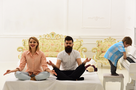 Young parents meditating, while their little son playing piano, annoying parents. Kid annoyed parents with noise. Mom and dad try to keep calm. Meditation concept. Couple do yoga exercises in bed.