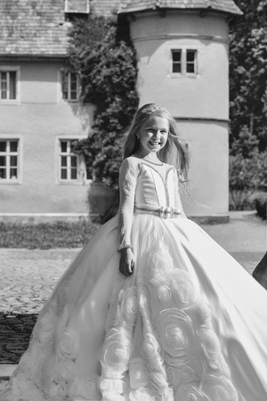 small girl kid with long blonde hair and pretty smiling happy face in prom princess white dress standing sunny day outdoor near building Stock Photo