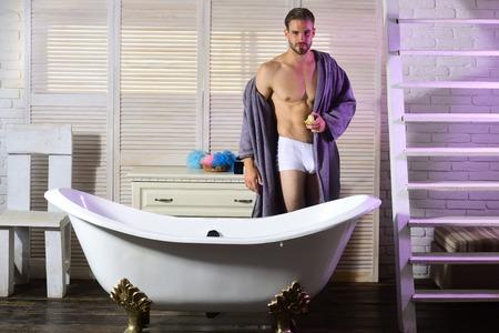 Man standing with apple fruit in bathroom.