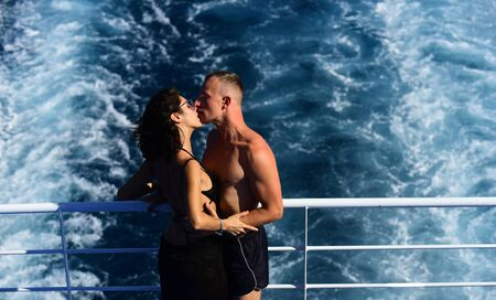 Attractive couple kissing and enjoy summer vacation. Honeymoon, just married concept. Couple stands on deck of cruise liner with sea waves on background. Couple in love travelling on cruise ship. Reklamní fotografie