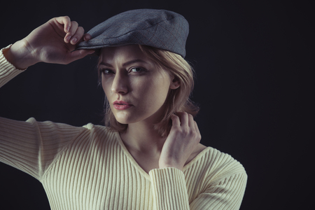 Woman on mysterious face wears kepi, dark background. Blonde lady looks like suspicious detective. Female logic concept. Girl thinking about investigation, copy space.