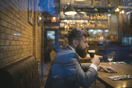 serious bar customer sit in cafe drinking ale. Beer time. Date meeting of hipster awaiting in pub. Businessman with long beard drink in cigar club. Bearded man rest in restaurant with beer glass.