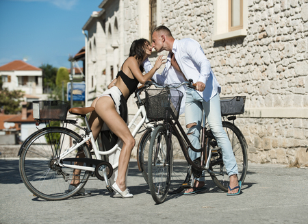 Sexy girl with naked buttocks rides bicycle, urban background. Attractive couple kiss while sit on bicycle. Fit and slim girl met handsome man on sunny day travelling by bicycle. Sexy couple concept.