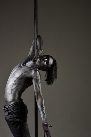 Performance concept. Man with nude torso covered with shimmering silver paint, dark background. Artistic guy hanging on metallis pole. Athlete, flexible sportsman performing pole dancing moves.