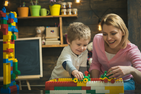 Mother and happy son play with constructor. Motherhood concept. Nursery with toys and chalkboard on background. Family playing with constructor at home. Mother and child play with toy cars, bricks.