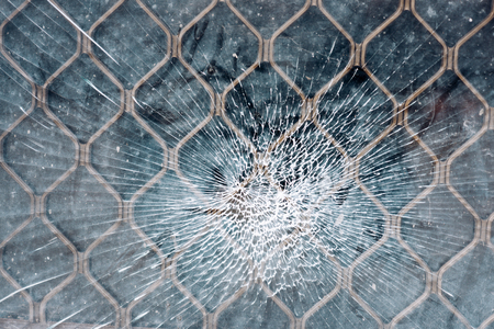Cracked window or glass as a spider web. Part of the old architecture. Metal grill or grate on the background. Urban vandalism concept. Фото со стока - 98774120