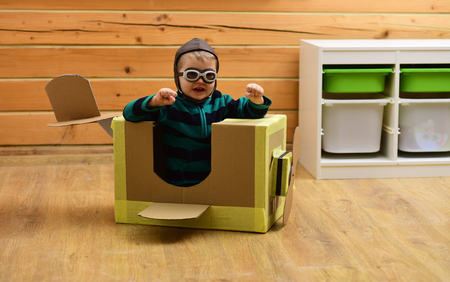 Pilot travel, airdrome, imagination. Little boy child play in cardboard plane, childhood. Dream, career, adventure, education. Air mail delivery, aircraft construction. Kid, pilot school, innovation.