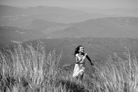 Little pretty happy smiling brunette girl in white lace summer dress running in mountain valley with deep dry spikelet grass in spring sunny day outdoo on natural blue background, horizontal picture