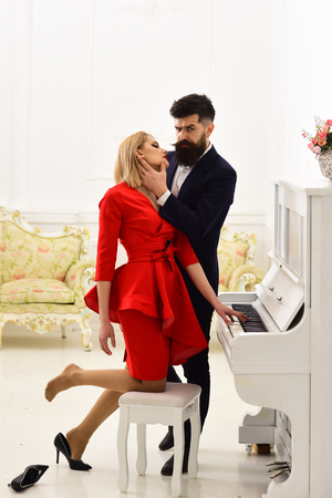 Elegant couple near piano, lady lost her shoe, luxury interior on background. Man in suit touches female face gently. Couple in love full of desire, enjoy piano music. Pianist concept. Lady play piano Stockfoto