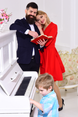 Child stand near piano keyboard, white interior background. Musician education concept. Rich parents enjoy parenthood. Boy adorable try to play piano musical instrument, while parents watching him.