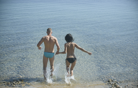 Couple in love running into sea water, sea surface on background, rear view. Couple topless run into sea with splashes of water. Vacation concept. Young family on honeymoon going to swim in ocean. Stockfoto
