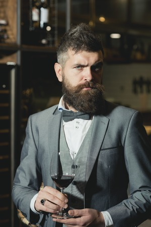 Confident winemaker in romantic atmosphere of cigar club. cigar club, serious winemaker with glass in business suit.