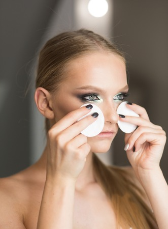 Look of pretty woman correct makeup. Look, woman use cotton pad for cleaning face skin.