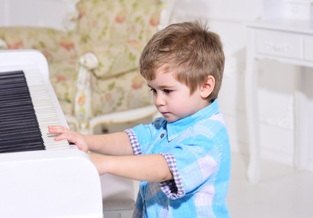 Child sit near piano keyboard, white background. Kid spend leisure near musical instrument. Boy cute and adorable puts finger on keyboard of piano. Elite childhood concept.