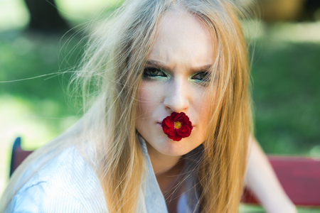 Girl with blonde hair and makeup hold red flower in mouth from blossoming tree in spring outdoor portrait
