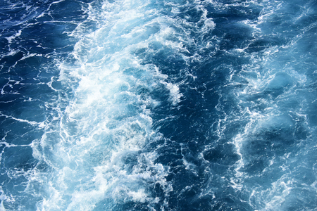 White foam of waves on blue ocean water. Texture of sea surface with waves. Beautiful background, sparkling, shimmering. Sea, ocean water texture. Background concept. Stock Photo