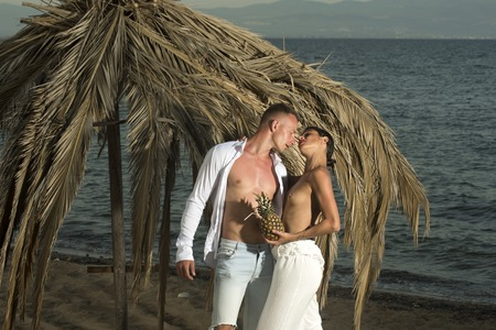 Couple in love full of desire at beach, sea background. Topless woman and man kissing near umbrella made out of dried palm leaves. Couple with pineapple on vacation at tropical seashore. Love concept. Stock Photo