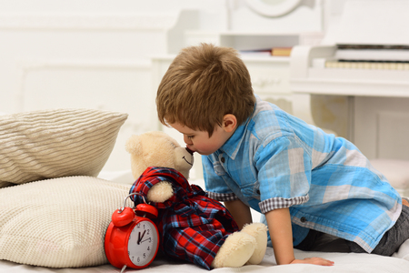 Child in bedroom kiss toy in nose. Good night concept. Boy with happy face puts favourite toy on bed, wishing sweet dreams. Kid put plush bear near pillows and alarm clock, luxury interior background. Stock Photo