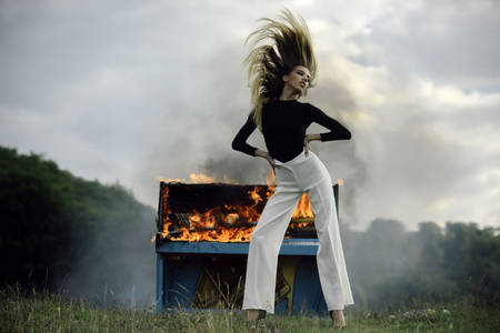 Woman in white pants at burning piano