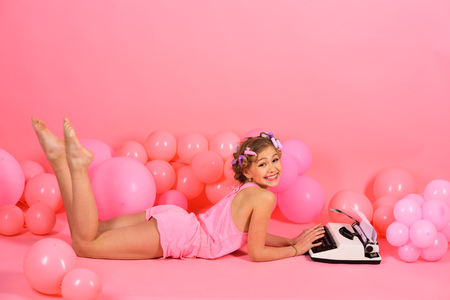 Child in underwear with typewriter on pink background. Kid journalist or writer, career. Education and childhood. Little girl secretary at party balloons. Small girl with curler in hair typing.